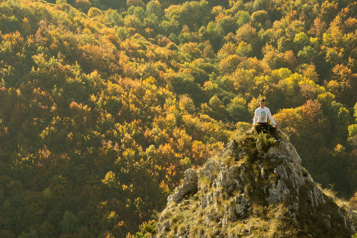 Front view of man meditating on cliff against autumn trees in forest