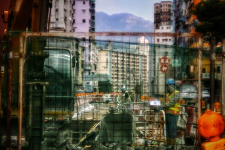 Nostalgic Hong Kong Series - I was born in this city where I no longer call home, yet the nostalgic part of the city is always attractive. Using a Canon FD lens to capture the moment enchance the mood. Fence Bokeh Streetphotography Nostalgia Urban The Street Photographer - 2018 EyeEm Awards Vintage Style Old Street Hong Kong Road Construction Road Sign City Window Reflection Architecture Building Exterior Built Structure Construction Vehicle Construction Equipment Traffic Cone Road Warning Sign