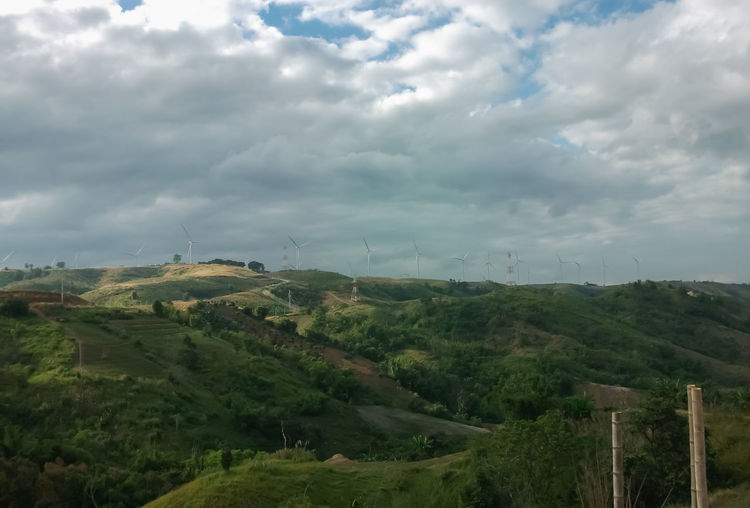 Architecture Beauty In Nature Built Structure Cloud - Sky Day Field Grass Green Color Growth Landscape Mountain Nature No People Outdoors Rural Scene Scenics Sky Tranquil Scene Tree Village Wind Turbine