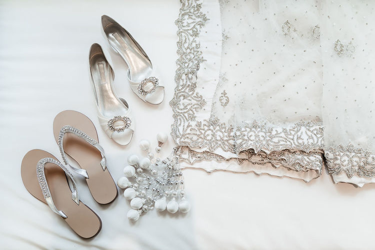 Directly above shot of dupatta and sandals on white textile