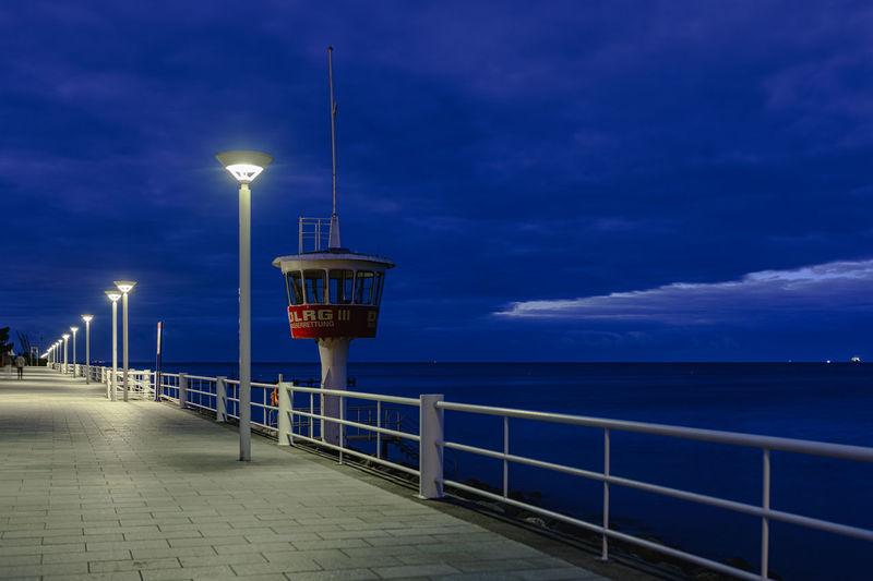 Illuminated street lights by sea against sky at dusk