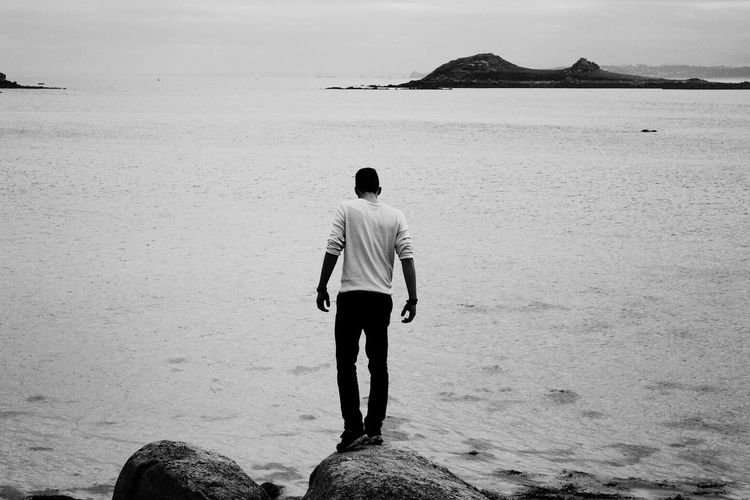 Full length rear view of man standing on rock overlooking sea
