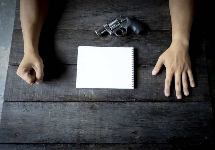 Close-up of businessman with gun and note pad on table