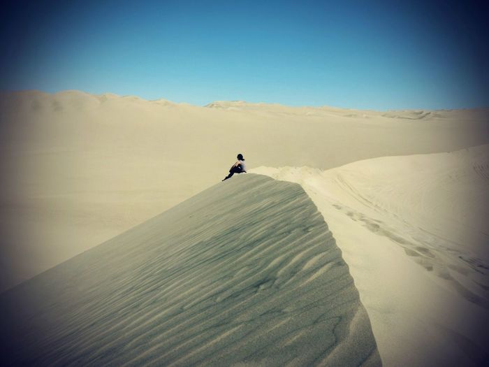 Woman sitting on sand dune at desert