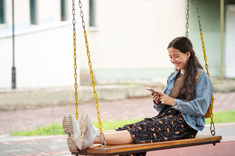 Young woman using smart phone on swing