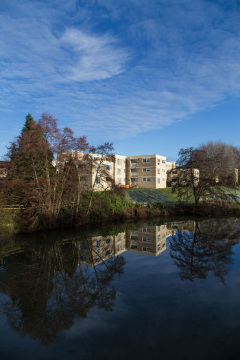 Tower block apartments reflected in blue river water Water Reflection Architecture Building Exterior Built Structure Sky Building Tree Waterfront Cloud - Sky Nature Plant Residential District No People Lake House Day Outdoors Blue Apartment
