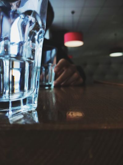 Close-up of person drinking glass on table