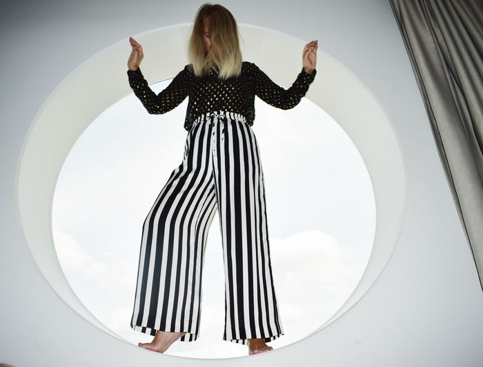 Striped Geometric Shape Window Circle One Person Rear View Human Arm Real People Standing Lifestyles Casual Clothing Full Length Women Arms Raised Sky