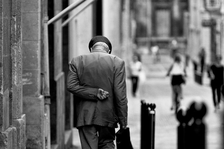 Rear view of old man walking on sidewalk