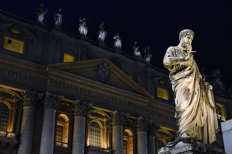 Low Angle View Of Statue Against St Peters Basilica In City At Night