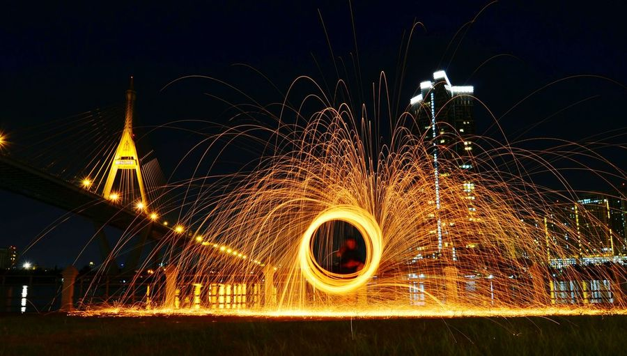 Wire wool spinning by chao phraya river with rama viii bridge in background