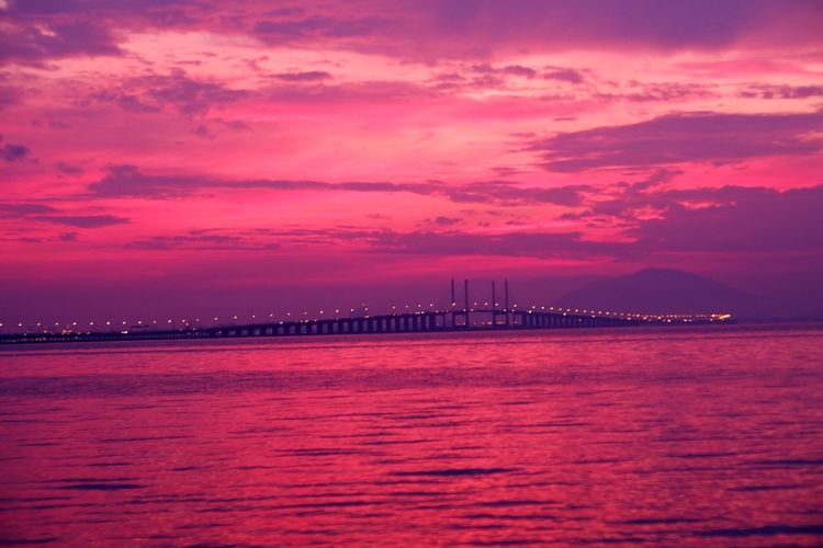View of bridge over sea against sunset sky