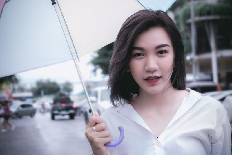girl's holding umbella Beautiful Woman Beauty Casual Clothing Day Focus On Foreground Front View Hairstyle Headshot Holding Lifestyles Looking At Camera Mode Of Transportation One Person Portrait Real People Transportation Women Young Adult Young Women