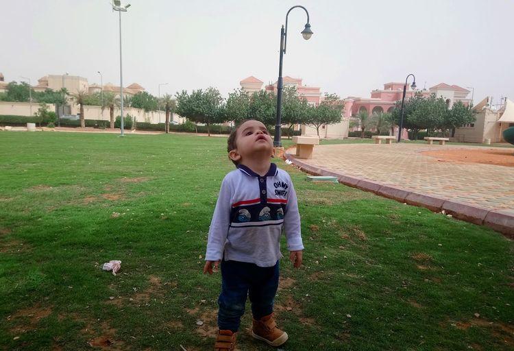 Boy standing on grass at park