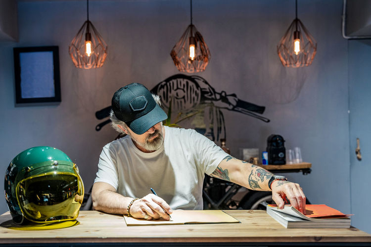 Man working on table against illuminated wall