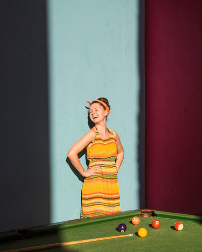 Woman laughing while standing by pool table