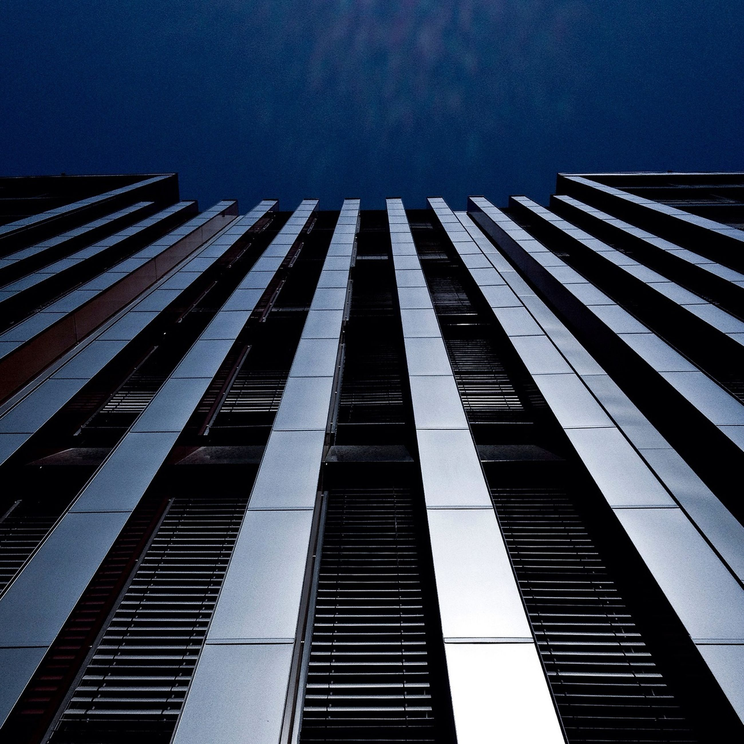 low angle view, architecture, built structure, building exterior, modern, office building, skyscraper, tall - high, city, tower, sky, building, glass - material, tall, reflection, outdoors, blue, day, no people, city life
