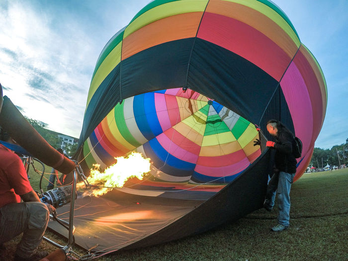 Adventure Burning Day Fire Fire - Natural Phenomenon Flame Heat - Temperature Holding Inflating Leisure Activity Lifestyles Men Motion Multi Colored Nature Outdoors People Real People Sky Two People