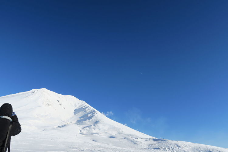 Man on snowcapped mountains against blue sky