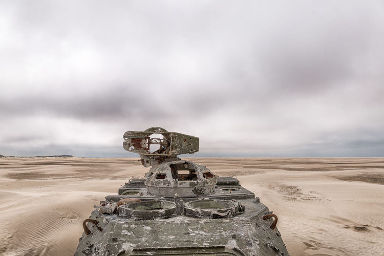 Abandoned armored tank at desert against cloudy sky
