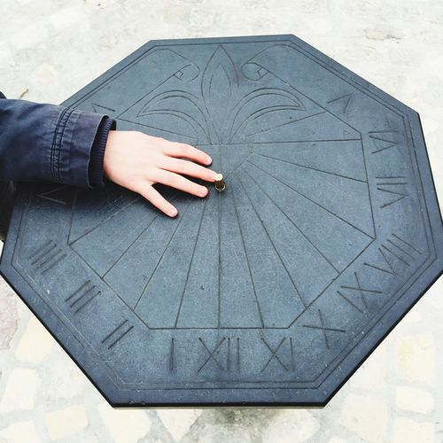 Cropped hand on sundial