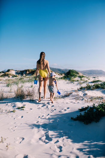 Rear view of mother and son walking on beach during sunny day