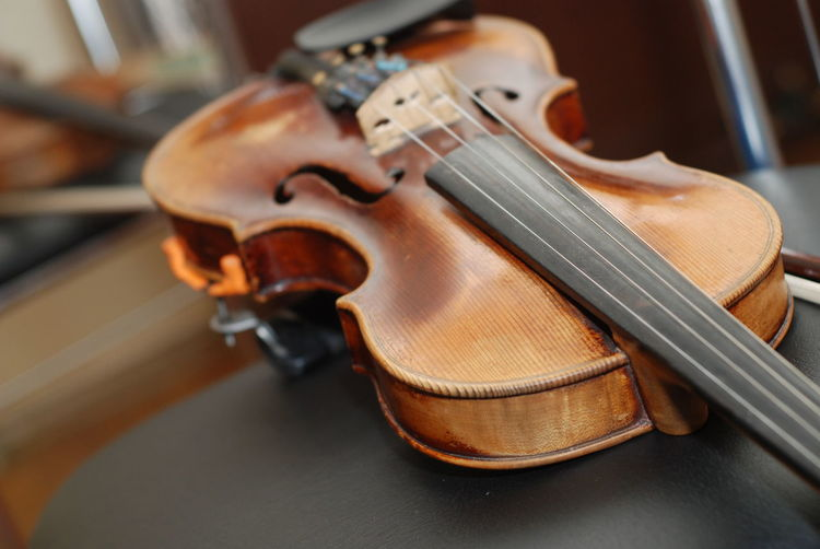Wooden violin lying on the black chair Classical Music Close-up Day Indoors  Instrument Maker Music Musical Instrument Musical Instrument String No People String Instrument Violin Wood - Material