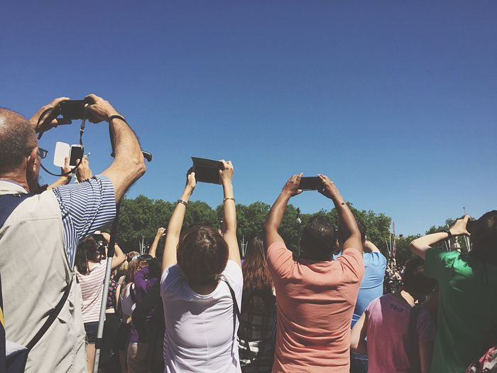 People photographing clear blue sky using cell phone