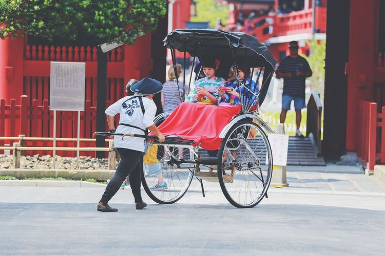 Woman pulling cart in city