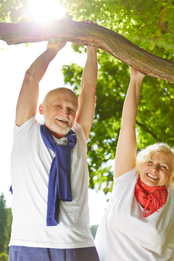 Low Angle Portrait Of Cheerful Senior Couple Hanging On Branch At Park
