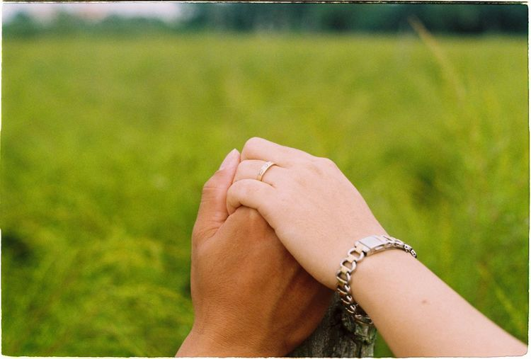 Close-Up Of Couple Holding Hand Against Grassy Field