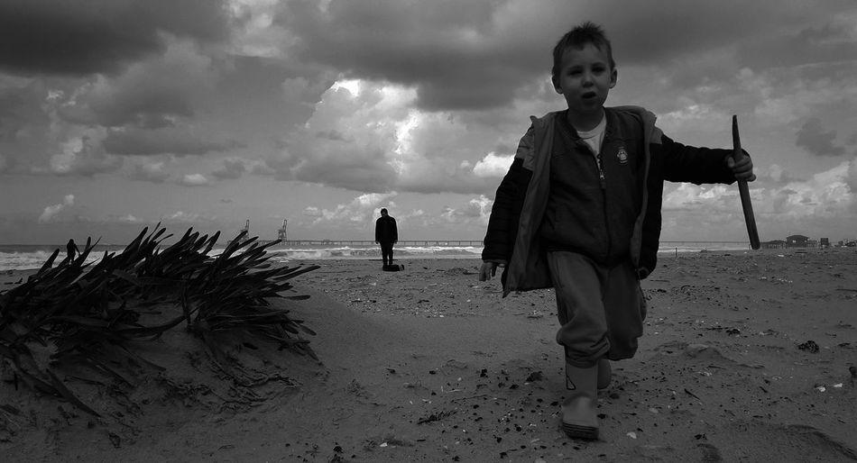 Boys standing on beach against sea