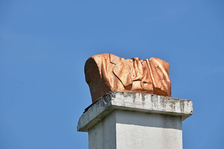 Low Angle View Of Broken Bust Monument Against Clear Blue Sky