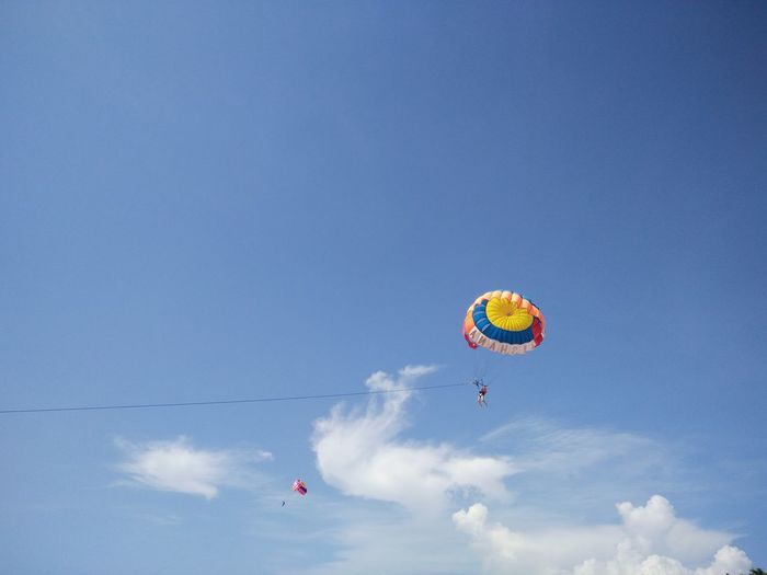 Low angle view of people parasailing against blue sky