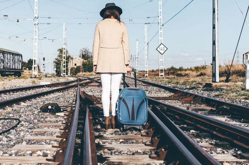 Rear view of a woman dressed with a grey hat walking with her suitcase along a railway track.