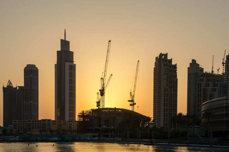 Modern Skyscrapers And Cranes By River During Sunset