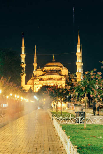Water fountain by footpath against illuminated sultan ahmed mosque at night