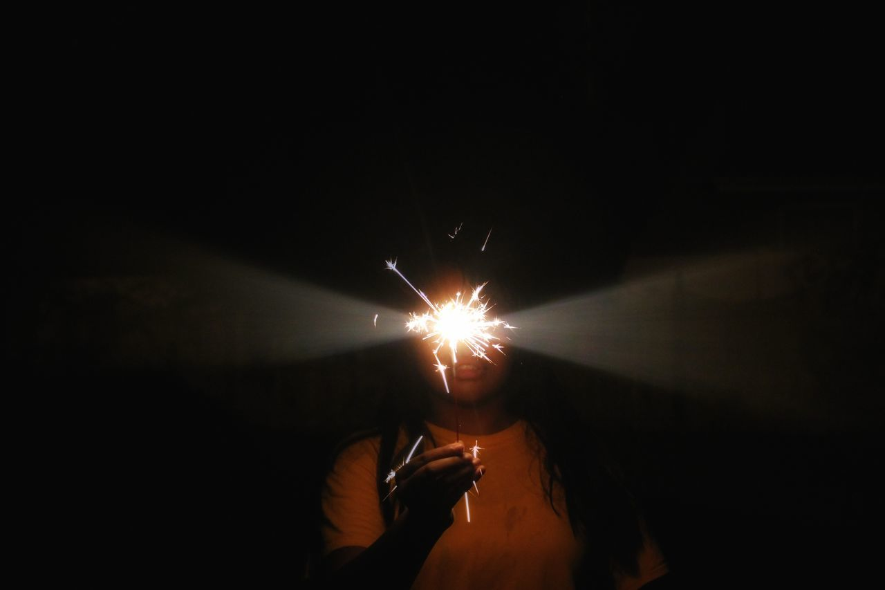 Woman holding lit sparkler at night