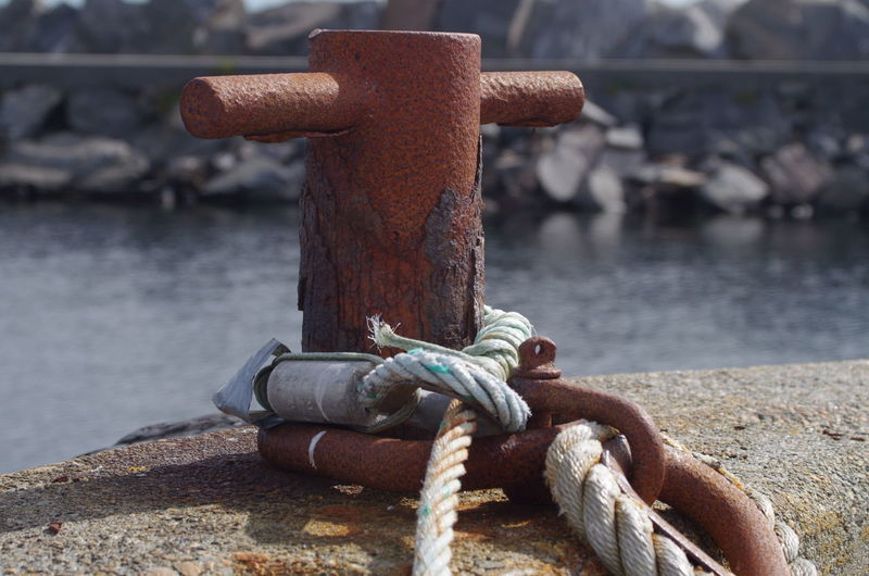 Close-up of rope tied up on metal bollard