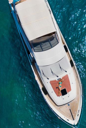 Woman lying on boat deck on sea