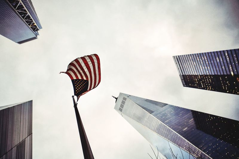 Low angle view of american flag amidst buildings against sky