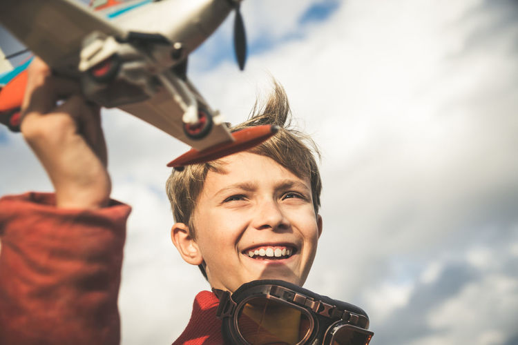 Little boy playing with a small plane in a sunny day, dreaming about being an airplane pilot and smiling at the camera. Young and happy kid with an hat thinking about planes and pilots. Headshot Portrait Smiling Happiness People Emotion Real People Young Adult Cloud - Sky Sky Leisure Activity Nature Day Men Young Men Lifestyles Holding Looking Adult Outdoors Vintage Glasses Aviator Pilot Playing