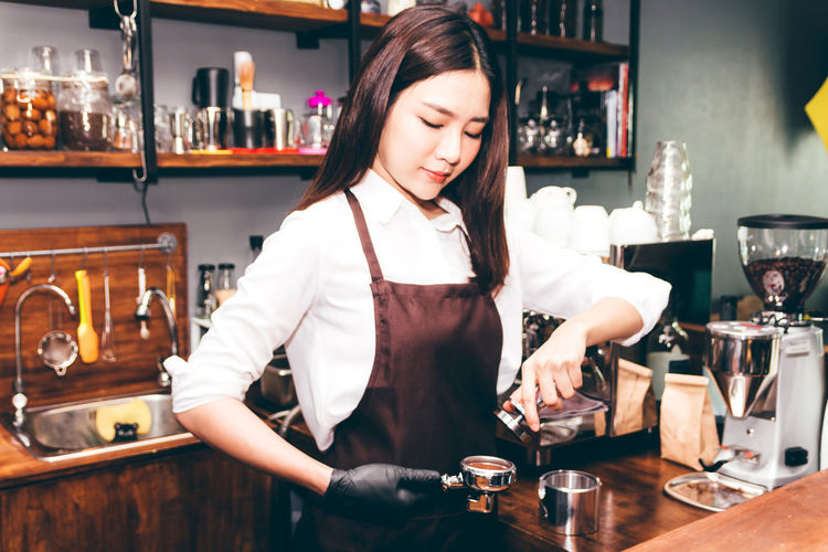 Women Barista using coffee machine for making coffee in the cafe Adult Alcohol Bar - Drink Establishment Bar Counter Bartender Beautiful Woman Business Drink Food And Drink Front View Glass Hairstyle Happy Hour Indoors  Occupation One Person Portrait Real People Refreshment Table Waist Up Women Young Adult Young Women
