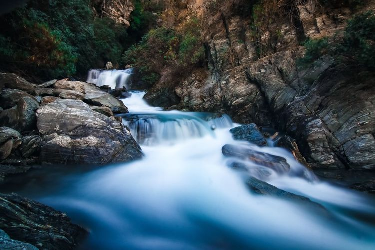 Beauty In Nature Blurred Motion Day Falling Water Flowing Flowing Water Forest Land Long Exposure Motion Nature No People Outdoors Power In Nature River Rock Rock - Object Scenics - Nature Solid Stream - Flowing Water Tree Water Waterfall