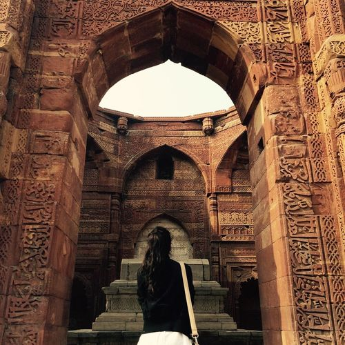 Rear view of woman standing by historic archway at qutb complex
