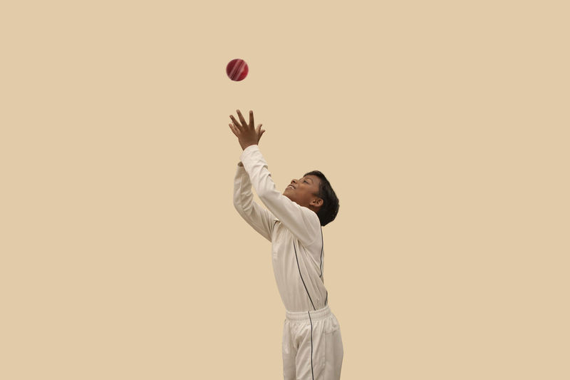 Man playing with ball against gray background