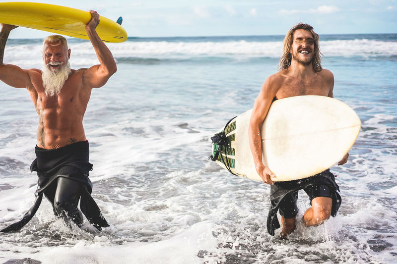 Shirtless men holding surfboards while walking in sea
