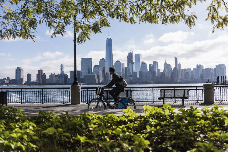 Man by modern buildings against sky in city