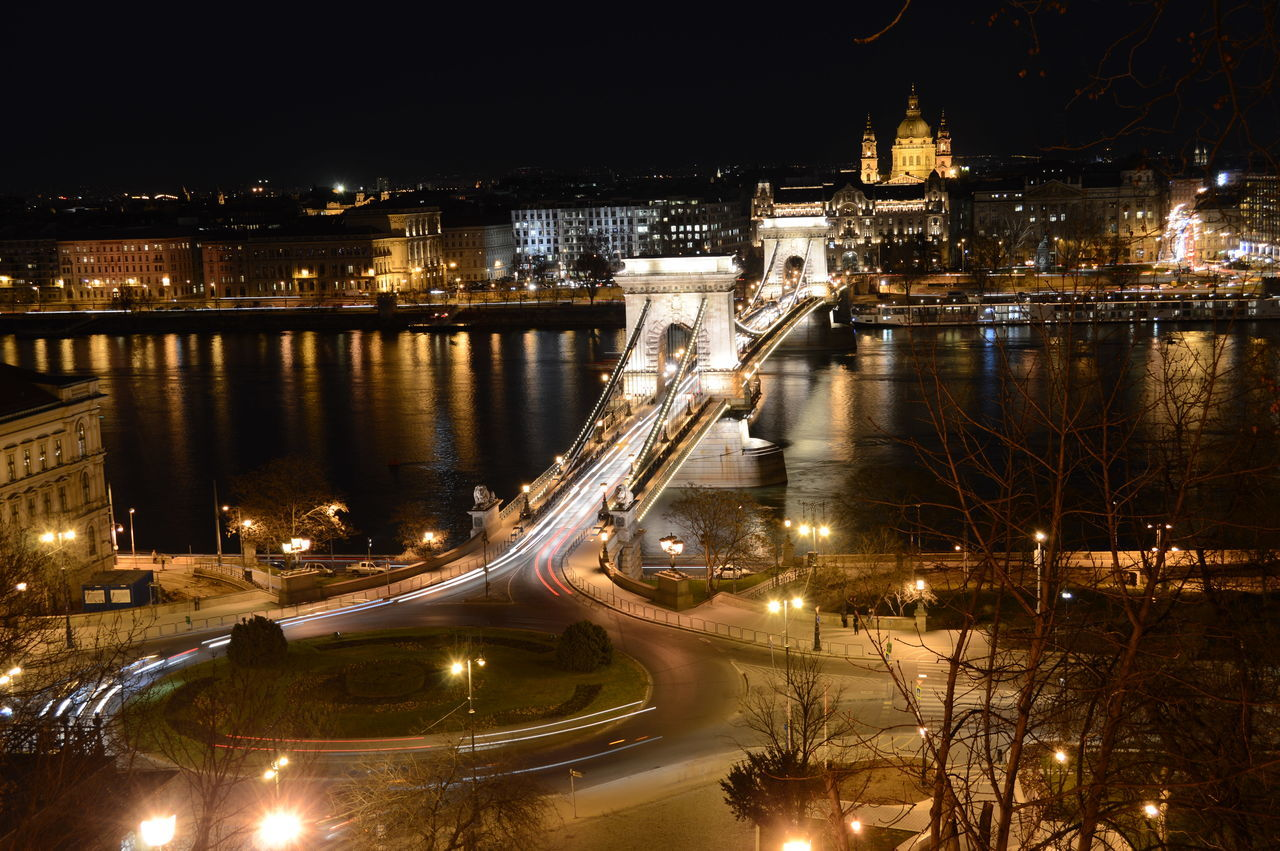 illuminated, night, architecture, bridge - man made structure, connection, built structure, chain bridge, water, transportation, building exterior, city, high angle view, outdoors, river, suspension bridge, sky, street light, travel destinations, no people, cityscape, tree