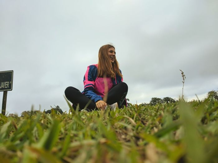 Low angle view of young woman sitting on grass against sky
